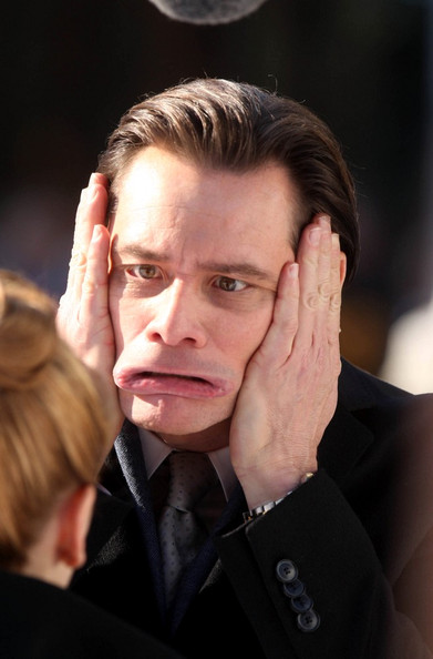 Jim Carrey pulls a variety of funny faces at co-star Ophelia Lovibond on the set of 'Mr Popper's Penguins'.