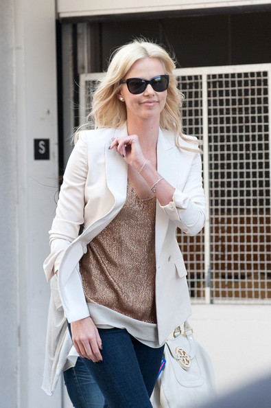 Charlize Theron loves her blazers! While heading to Comic-Con the actress opted for a crisp white style over a gold tank.