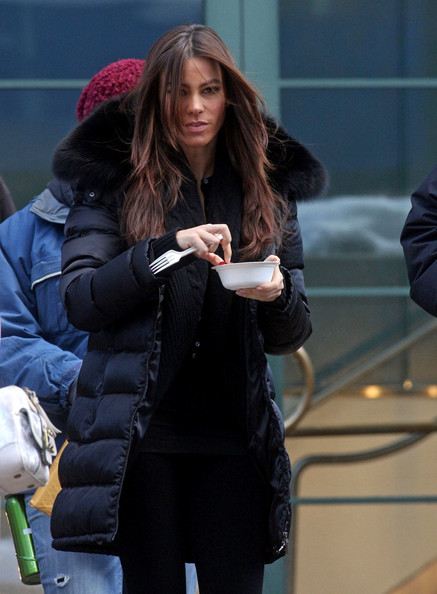 "Katherine Heigl and Sofia Vergara stay bundled up in their winter best as they walk around the set of their upcoming film, ""New Year's Eve."" At one point Heigl tries to cover up and avoid the cameras while Vergara is happy to snack on some strawberries."