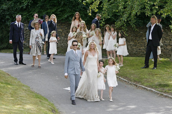 Kate Moss looks like the stunning glowing bride as she passionately kisses her husband Jamie Hince with her bridal party after exchanging marriage vows at St Peter's parish church.
