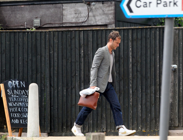 Jude Law takes a train from London to Surrey then walks to the nearest taxi.