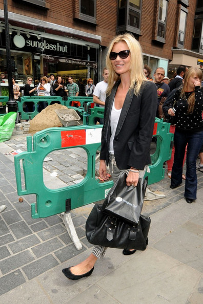 Kate Moss causes a stir with fans as she goes shopping at Sunglass Hut in Covent Garden.