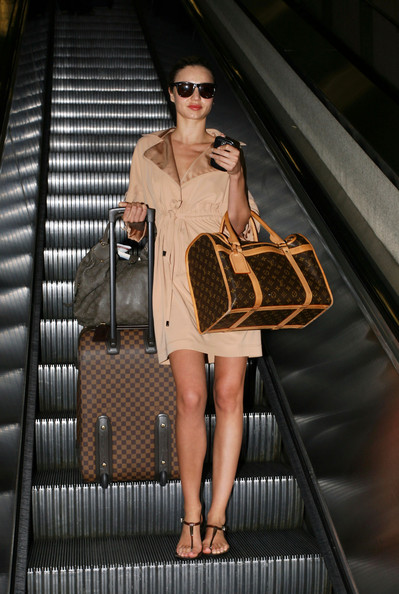"Miranda Kerr looks like she stepped off a runway when she arrived to Los Angeles with her puppy ""Frankie"" under her arm."