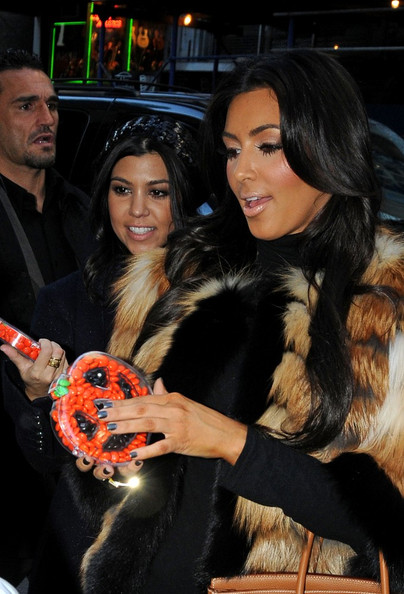 Kourtney Kardashian Kourtney and Kim Kardashian leave a Midtown recording studio.  On the way out, they are given some Halloween candy and gifts from a fan.
