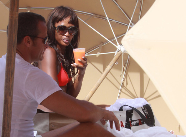 Supermodel Naomi Campbell and her boyfriend Vladislav Doronin hide behind the cover of beach umbrellas in attempt to enjoy the sun without the eye of the cameras.