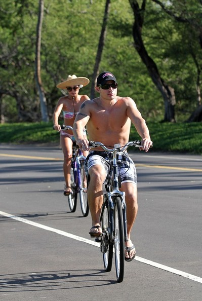 Nick Lachey Nick Lachey and Vanessa Minnillo show off their toned physiques as they go for a bike ride in their bathing suits. Nick goes shirtless in plaid board shorts, while Vanessa pairs her floral bikini with a straw sunhat.