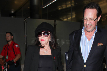 Percy Gibson Joan Collins and Percy Gibson Are Seen at LAX