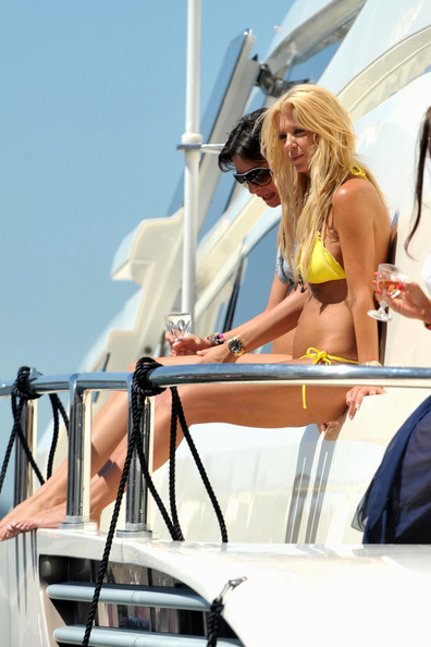 Tara Reid sports a bright yellow bikini aboard a yacht with friends and her current mystery male companion, with whom she gets a little cozy.