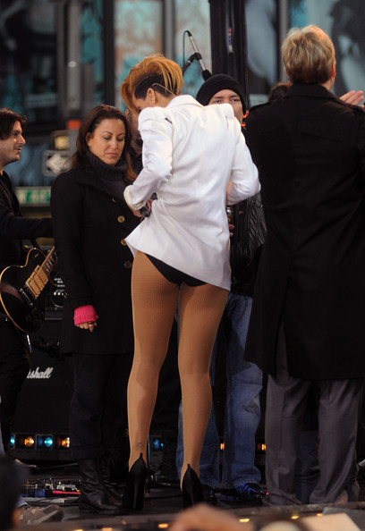 Rihanna performs for a large crowd of fans when she makes a guest appearance on Good Morning America. At one point the singer consults with a production assistant as she appears to have trouble with her wardrobe.