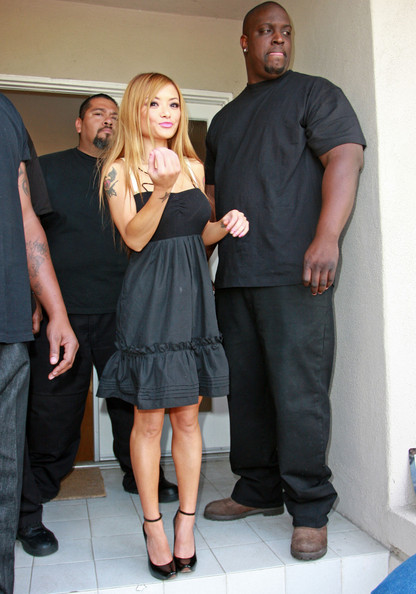 Tila Tequila is protected by two huge body guards as she holds a garage sale at her home.  The large gathering attracts the attention of local police officers.