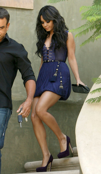 Actress Vanessa Hudgens descends stairs wearing a very short blue dress and