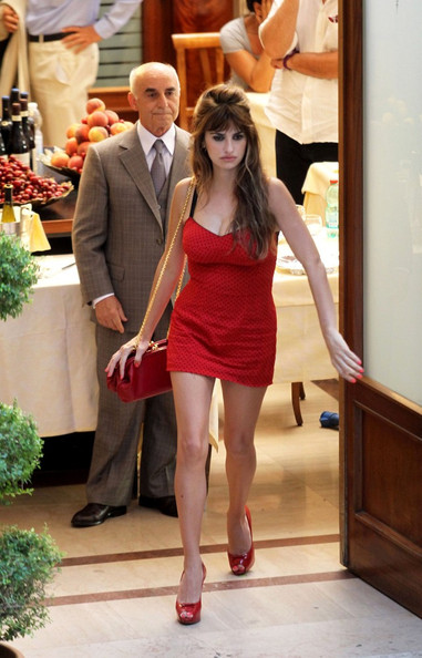 "Penelope Cruz shows off a lot of leg in a short red mini dress while filming Woody Allen's latest movie ""Bop Decameron."" Cruz smiles and listens intently as Allen gives her direction for the scene."