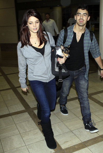 Couple Joe Jonas and Ashley Greene arriving on a flight at LAX airport in Los Angeles, CA. Ashley has her dog with her in a little purse. Joe helps put a necklace on while they wait for their bags. The couple is also seen holding hands.
