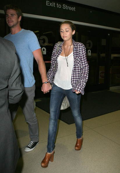 Singer/actress Miley Cyrus and her boyfriend Liam Hemsworth hold hands as they arrive at LAX to catch a late night flight to Toronto. Miley is set to host the 2010 Much Music Video Awards.