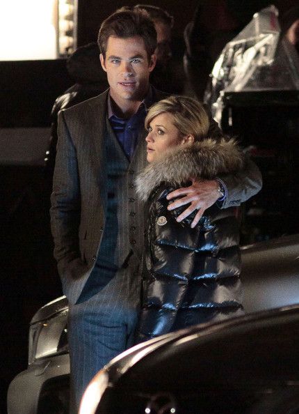 Actress Reese Witherspoon and Chris Pine on the set of 'This Means War' in Vancouver, Canada. In this scene Reese is writing her number on Chris' hand. In between takes Reese pretends to read Chris' palm with gives the two a good laugh. At the end of the night they have to be protected with an umbrella from a bodyguard as the rain comes crashing down just as they look up. Also on the set earlier is actor Tom Hardy.