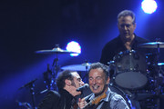 """Nils Lofgren,and  Bruce Springsteen perform at """"12-12-12"""" a concert benefiting The Robin Hood Relief Fund to aid the victims of Hurricane Sandy presented by Clear Channel Media & Entertainment, The Madison Square Garden Company and The Weinstein Company at Madison Square Garden on December 12, 2012 in New York City."""
