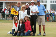 Phil Mickelson of the United States holds the Claret Jug wife Amy and children Evan, Amanda and Sophia, manager Steve Loy, coach Butch Harmon and caddie Jim Mackay after winning the 142nd Open Championship at Muirfield on July 21, 2013 in Gullane, Scotland.