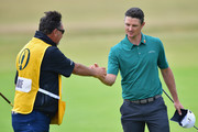Justin Rose of England with his caddie Mark Fulcher on the 18th green during the third round of the 147th Open Championship at Carnoustie Golf Club on July 21, 2018 in Carnoustie, Scotland.