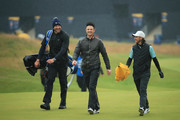 (L-R) Ian Finnis, caddie of Tommy Fleetwood, Justin Rose of England and Tommy Fleetwood of England walk down the fairway during a practice round prior to the 148th Open Championship held on the Dunluce Links at Royal Portrush Golf Club on July 17, 2019 in Portrush, United Kingdom.
