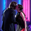 She gives kisses to Christian Bale.