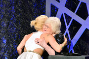 Winner of the award for Excellence in Costume Design for Fantasy Film, The Hunger Games: Catching Fire, Trish Summerville accepts the award from actress June Squibb onstage during the 16th Costume Designers Guild Awards with presenting sponsor Lacoste at The Beverly Hilton Hotel on February 22, 2014 in Beverly Hills, California.