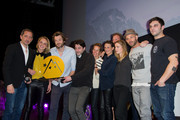 (L-R) Actor Gad Elmaleh, French producers Maxime Govare, Noemie Saglio, unidentified person, Camille Cottin, Adrianna Gradziel, Franck Gastambide and Pio Marmai pose with the 'OCS Festival de l'Alpe d'Huez 2015' prize for their movie 'Toute premiere fois' during the closing ceremony of the 18th L'Alpe D'Huez International Comedy Film Festival in l'Alpe d'Huez, France.