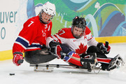 Eskil Hagen #7 of Norway controls the puck against Brad Bowden #27 of Canada during the second period of the Ice Sledge Hockey Bronze Medal Game between Norway and Canada on day eight of the 2010 Vancouver Winter Paralympic Games at UBC Thunderbird Arena on March 19, 2010 in Vancouver, Canada.
