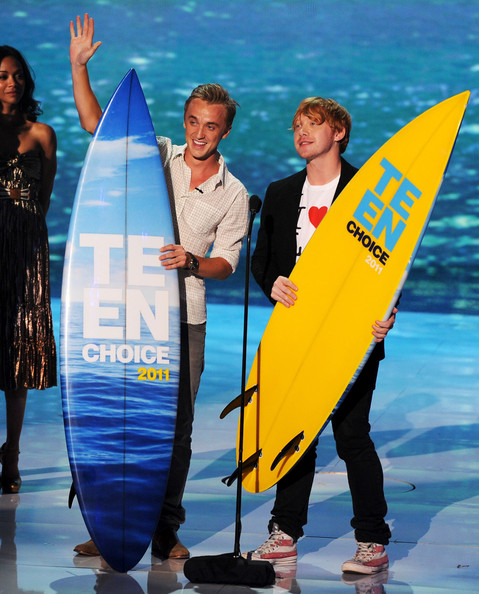 Actors Tom Felton (L) and Rupert Grint accept the Harry Potter awards onstage during the 2011 Teen Choice Awards held at the Gibson Amphitheatre on August 7, 2011 in Universal City, California.