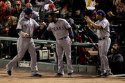 (L-R) Josh Hamilton #32 of the Texas Rangers celebrates with Elvis Andrus #1 and Yorvit Torrealba #8 after scoring on an RBI double by Michael Young #10 in the first inning during Game Seven of the MLB World Series against the St. Louis Cardinals at Busch Stadium on October 28, 2011 in St Louis, Missouri.
