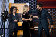 Carrie Underwood (C) accepts Favorite Female Artist - Country from Sara Gilbert (L) and Thomas Rhett (R) onstage during the 2018 American Music Awards at Microsoft Theater on October 9, 2018 in Los Angeles, California.