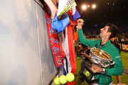 Novak Djokovic of Serbia signs autographs for fans on Margaret Court Arena as he holds the Norman Brookes Challenge Cup after winning the Men's Singles Final against Dominic Thiem of Austria on day fourteen of the 2020 Australian Open at Melbourne Park on February 02, 2020 in Melbourne, Australia.