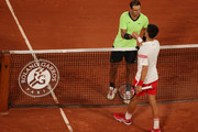 Novak Djokovic of Serbia (R) shakes hands with Rafael Nadal of Spain after winning their Men's Singles Semi Final match against on day Thirteen of the 2021 French Open at Roland Garros on June 11, 2021 in Paris, France.