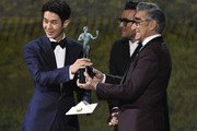 (L-R) Choi Woo-shik accepts Outstanding Performance by a Cast in a Motion Picture for 'Parasite' from Dan Levy and Eugene Levy onstage during the 26th Annual Screen Actors Guild Awards at The Shrine Auditorium on January 19, 2020 in Los Angeles, California. 721359