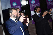 """Judd Apatow stands with photographers and takes photos of Leslie Mann on the red carpet at the Closing Night Screening of """"The Comedian"""" at the 28th Annual Palm Springs International Film Festival on January 15, 2017 in Palm Springs, California."""