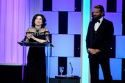 Honoree Sue Kroll (L) accepts the Sid Grauman Award as actor Bradley Cooper looks on onstage at the 30th Annual American Cinematheque Awards Gala at The Beverly Hilton Hotel on October 14, 2016 in Beverly Hills, California.
