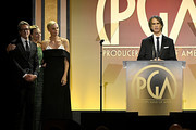 (L-R) Honoree Charles Randolph, Margot Robbie, and honoree Charlize Theron listen while honoree Jay Roach accepts the Stanley Kramer Award for 'Bombshell' onstage during the 31st Annual Producers Guild Awards at Hollywood Palladium on January 18, 2020 in Los Angeles, California.