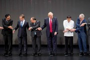 (L-R) Thailand's Prime Minister Prayut Chan-O-Cha, Russian Prime Minister Dmitry Medvedev, Vietnam's Prime Minister Nguyen Xuan Phuc, US President Donald Trump, Philippine President Rodrigo Duterte and Australia Prime Minister Malcolm Turnbull join hands for the family photo during the 31st Association of South East Asian Nations (ASEAN) Summit in Manila on November 13, 2017. .World leaders are in the Philippines' capital for two days of summits.  / AFP PHOTO / JIM WATSON