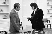 380450 05: Elvis Presley shows President Richard Nixon his cuff links December 21, 1970 at the White House.