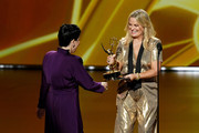 Alex Borstein accepts the Outstanding Supporting Actress in a Comedy Series award for 'The Marvelous Mrs. Maisel' from Amy Poehler onstage during the 71st Emmy Awards at Microsoft Theater on September 22, 2019 in Los Angeles, California.