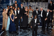Director Steve McQueen (C) accepts the Best Picture award for '12 Years a Slave' with (back row) actors Sarah Paulson, Benedict Cumberbatch, Lupita Nyong'o, screenwriter John Ridley, actor Chiwetel Ejiofor, producers Arnon Milchan, Dede Gardner, Jeremy Kleiner and Anthony Katagas, actress Adepero Oduye and producer Brad Pitt onstage during the Oscars at the Dolby Theatre on March 2, 2014 in Hollywood, California.
