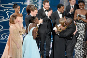 Director Steve McQueen (R) embraces producer Bianca Stigter as they accept the Best Picture award for '12 Years a Slave' with (back row) actors Sarah Paulson, Kelsey Scott, Lupita Nyong'o, Benedict Cumberbatch, Michael Fassbender, Chiwetel Ejiofor, Paul Dano, and Adepero Oduye onstage during the Oscars at the Dolby Theatre on March 2, 2014 in Hollywood, California.