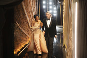 In this handout photo provided by A.M.P.A.S. Regina King and Best Actor in a Supporting Role winner Brad Pitt walk backstage during the 92nd Annual Academy Awards at the Dolby Theatre on February 09, 2020 in Hollywood, California.
