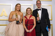 """Reese Witherspoon (center) poses with Dana Murray (L) and Pete Docter (R), winners of Animated Feature Film for """"Soul,"""" in the press room at the Oscars on Sunday, April 25, 2021, at Union Station in Los Angeles."""