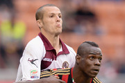 Mario Balotelli of AC Milan and Djamel Mesbah of AS Livorno Calcio (L) during the Serie A match between AC Milan and AS Livorno Calcio at San Siro Stadium on April 19, 2014 in Milan, Italy.