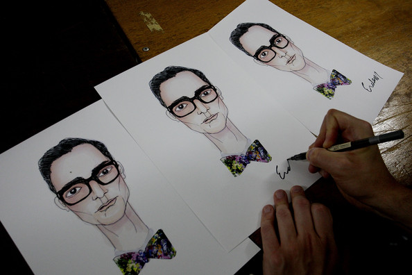Designer Erdem Moralioglu signs a drawing of himself backstage ahead of the Erdem show during Audi Fashion Festival Singapore 2011 at Tent@Orchard on May 14, 2011 in Singapore.
