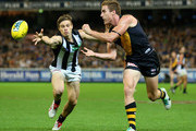 Daniel Jackson of the Tigers handballs whilst being tackled by Josh Thomas of the Magpies during the round four AFL match between the Richmond Tigers and the Collingwood Magpies at Melbourne Cricket Ground on April 11, 2014 in Melbourne, Australia.