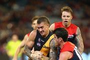 Dustin Martin of the Tigers is tackled by Nathan Jones and Angus Brayshaw of the Demons  during the round five AFL match between the Melbourne Demons and the Richmond Tigers at Melbourne Cricket Ground on April 24, 2016 in Melbourne, Australia.