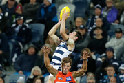Jack Henry of the Cats takes a high mark over Matt de Boer of the Giants during the 2018 AFL round seven match between the Geelong Cats and the GWS Giants at GMHBA Stadium on May 4, 2018 in Geelong, Australia.