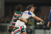 Gerherd Vosloo of Clermont Auvergne passes the ball as he is tackled by Toby Flood and Ben Youngs during the Heineken Cup match between ASM Clermont Auvergne and Leicester Tigers at Stade Marcel Michelin on December 11, 2011 in Clermont-Ferrand, France.