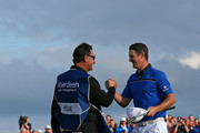 Justin Rose of England celebrates with his caddie Mark Fulcher on the 18th hole after winning the 2014 Aberdeen Asset Management Scottish Open at Royal Aberdeen Golf Club on July 13, 2014 in Aberdeen, Scotland.